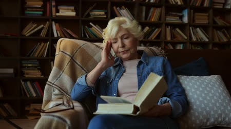 defter : Involved in thoughts. Concentrated pleasant elderly woman sitting in the arm chair and reading a book while feeling tired Stok Video