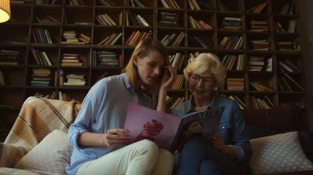 зрелом возрасте : Beauty trends. Joyful nice woman amd her elderly mother reading a fashion magazine while resting together at home Стоковые видеозаписи