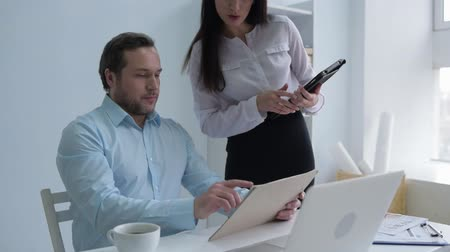 destruição : Office solicitation. Young lady with a tablet computer undoing buttons on her blouse and sitting on a table of her boss while flirting with him at work.