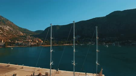 drove : A large yacht stands at the pier in the bay Kotor, Montenegro. Aerial footage Stock Footage