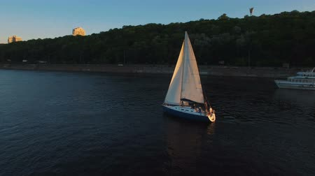 lanoví : Sailing yacht with white sails swims along the river at sunset aerial
