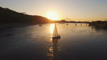 парусное судно : Sailing yacht with white sails swims along the river at sunset aerial