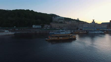 kiev : Excursion passenger ship sails to the port of the old European city at sunset Stock Footage