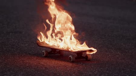 kicked : Skateboard set on fire slowly moving along the street Stock Footage