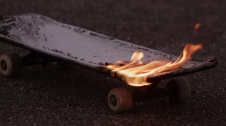 kicked : Flaming skateboard put out by a boy Stock Footage