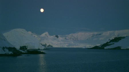 buz : North pole scenery. Snow covered coast, moon reflecting in the water Stok Video