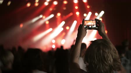 festivais : Summer music festival, people listening to the concert. Young man video recording with his smartphone
