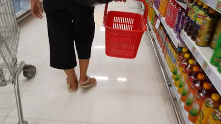walmart : Bangkok, Thailand. November 19,2017. beautiful asian women holding red basket and looking for food on the shelf to buy in the supermarket. Stock Footage