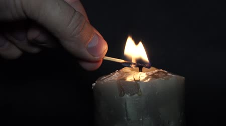 cemitério : A candle is ignited by a match