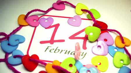 wasknijper : February 14 covered with colored plastic hearts, Valentines Day background