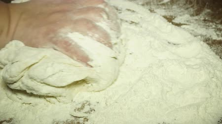 assar : Close up view of married baker's hands kneading the dough on the table. Manufacturing process, working hard. Making bread, bread production. Workplace. Beautiful view.