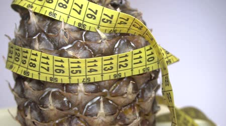 milimetre : Tape measure wrapped around rotating pineapple, loopable - 1080p Stok Video