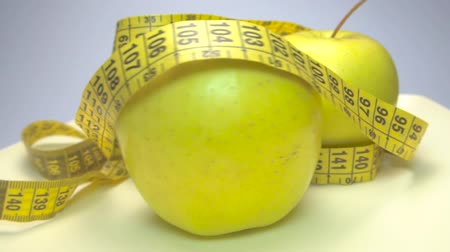 centímetro : Green, juicy and fresh apple with measuring tape on white background, rotation