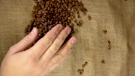 instante : human hands to touch high-quality coffee beans to scatter, bag jute, slow motion