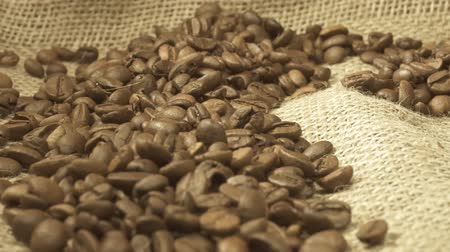 黄麻布 : A handful of brown, roasted coffee beans on burlap sacking background, macro close up, rotation.