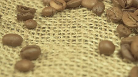 sznurek : Top view of messy pile of freshly roasted brown coffee beans on textured canvas textile