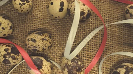 Easter eggs with a ribbon on a rag background with straw Стоковые видеозаписи
