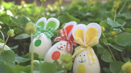 ornamento : Cute Easter bunny ornaments and Easter Eggs on white table against garden background in the breeze, static.