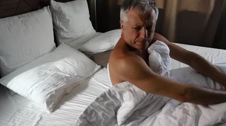 bed linen : A man wakes up and stretches. Stock Footage