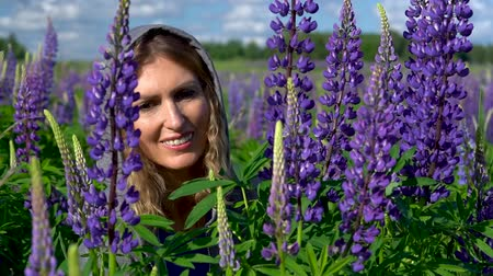 hayran olmak : A beautiful woman, admires the purple flowers in the meadow on a Sunny day and smiles. Face and flowers closeup.
