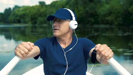 ひげを剃っていない : A slender gray-haired man in white headphones, a blue cap, a t-shirt and glasses rowing oars on a white boat on the river on a summer day, listening to music and singing a song.