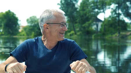 ひげを剃っていない : Happy slender gray-haired man in a blue t-shirt and glasses rowing on a white boat on the river on a summer day and admires the surrounding nature.