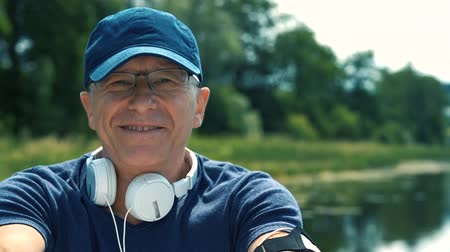 não barbeado : A slender gray-haired man in white headphones, a blue cap, a t-shirt and glasses rowing oars on a white boat on the river on a summer day, listening to music and singing a song.