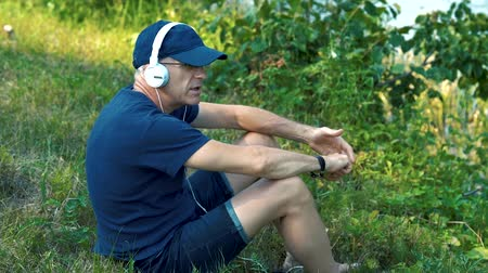 ひげを剃っていない : A slender gray-haired man in white headphones, a blue t-shirt, a cap and glasses sits on the green grass on the Bank of the river on a summer day, listens to music, sings and admires nature.