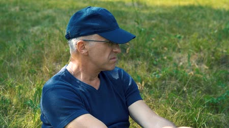 looking distance : A slender, serious gray-haired man in a blue t-shirt, cap and glasses sits on the green grass in the forest on a summer day, looks into the distance and thinks. Stock Footage
