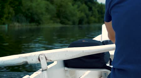 remo : A man in a blue t-shirt quickly rowing on a boat on the river white paddle summer day. Vídeos