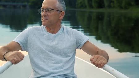 saçlı : A slender gray-haired serious man in a gray t-shirt and glasses rowing on a white boat on a calm river on a summer evening at sunset and admires nature.