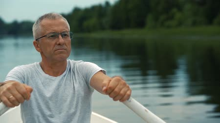небритый : A slender gray-haired serious man in a gray t-shirt and glasses rowing on a white boat on a calm river on a summer evening at sunset and admires nature.
