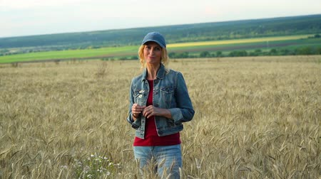 delgado : A slender woman in jeans and a cap stands on a wheat field, smiling and holding chamomile flowers on a Sunny summer day.