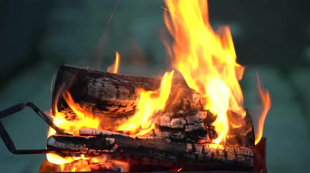 In the grill with a strongly burning wood man corrects tongs firewood and puts it in the fire new burning coals. Stock Footage