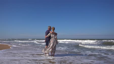 A slender man and a woman in a long dress stand embracing on a sandy beach in the rolling waves of the sea in the wind talking and smiling on a Sunny summer day.