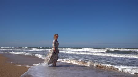 A slender woman in a long dress fluttering in the wind stands on a sandy beach in the waves running over her feet and smiles at the summer Sunny days.