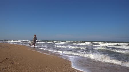 A slender woman in a long light dress is walking along the sandy beach on the incoming waves of a summer day.