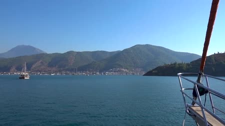 fethiye : Beautiful yacht quickly sails on the blue sea to the shore with beautiful mountains and white houses on a clear Sunny day. The bow of the yacht closeup. Stock Footage