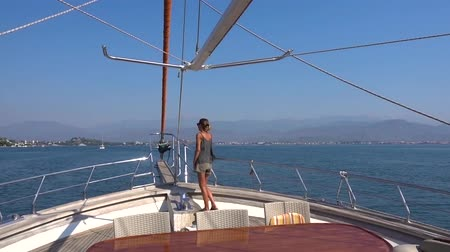 fethiye : A slim, tanned woman in sunglasses stands at the bow of the yacht and looks out at the approaching coast with mountains on a Sunny day. Stock Footage