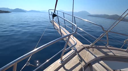 The yacht quickly sails across the blue sea towards the small Islands on a clear Sunny day. The bow of the yacht closeup.
