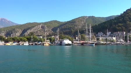 fethiye : A large port with yachts, ships and boats against the backdrop of beautiful mountains, white houses and blue sea on a Sunny day in Turkey.