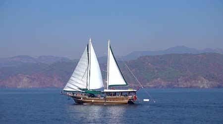 mastro : Beautiful big sailing ship with white sails is sailing fast on the blue sea on the background of beautiful low mountains and Sunny day in Turkey.