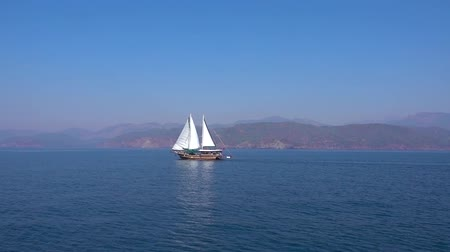 fethiye : Beautiful big sailing ship with white sails is sailing fast on the blue sea on the background of beautiful low mountains and Sunny day in Turkey.