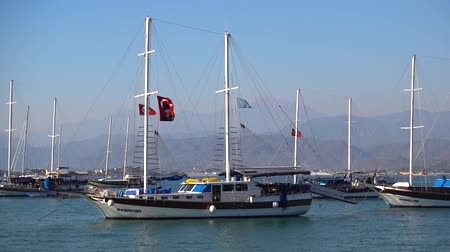 winch : A beautiful big ship with a waving Turkish red flag on the mast is anchored in the port on a calm blue sea against the backdrop of beautiful mountains and yachts on a Sunny day in Turkey. Stock Footage