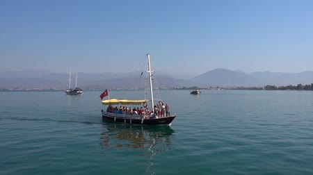 fender : A small pleasure boat with a group of cheerful travelers, sailing on a calm blue sea against the backdrop of beautiful small mountains and yachts on a Sunny day in Turkey. Stock Footage
