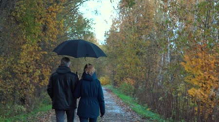 saçlı : A slender, gray-haired man with glasses and a slender, pretty, middle-aged woman walk along an autumn Park Avenue under a black umbrella, admiring nature, talking and smiling.
