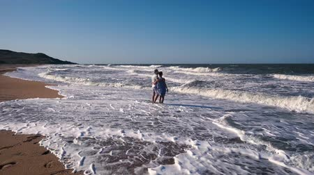 meia idade : A slender couple, a man in shorts and a woman in a blue dress walk barefoot in a strong wind on a sandy beach and admire the sea waves on a Sunny summer day.
