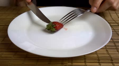 A man eats strawberries with a fork and a knife from a large white plate. Stockvideo
