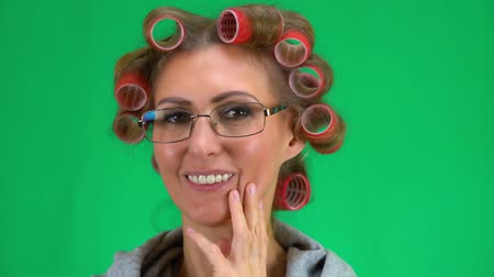 meia idade : A middle-aged woman with curlers on her head tries on your glasses and rejoice. Female face close-up. The background is chroma key.