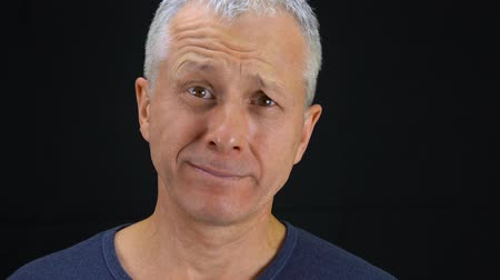 The face of a middle-aged man with gray hair and brown eyes depicts different human emotions. The man winces. Face close-up.